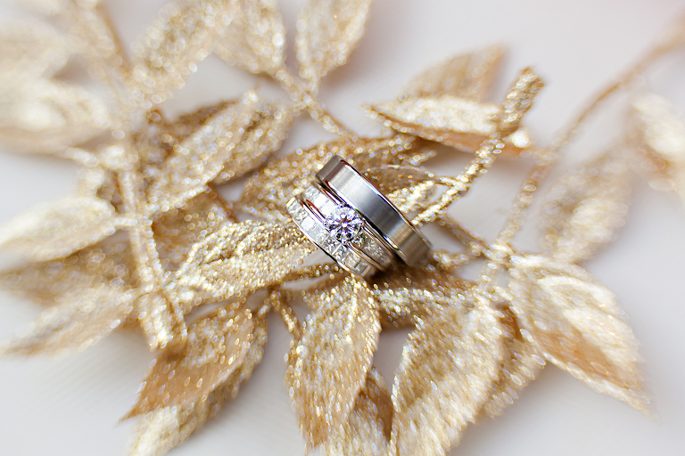 wedding rings detailed on gold glitter leaves