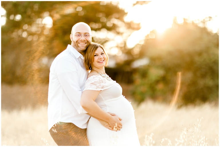 maternity portrait of couple with lens flare