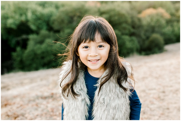 portrait of little girl in blue top and faux fur vest at mini session